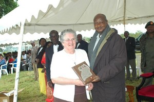 Miriam Duggan receives award from President Museveni