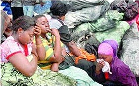 Women sit despondent as fire rages
